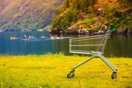 85865292-random-shopping-cart-trolley-in-nature-norwegian-green-background-landscape-tourism-buying-concept-.jpg